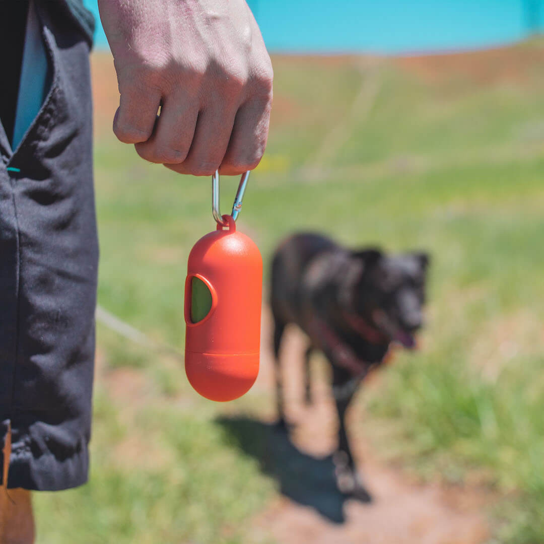person holding a poop bag holder with poop bags | Pupford